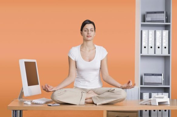 Woman sitting on desk next to computer meditating
